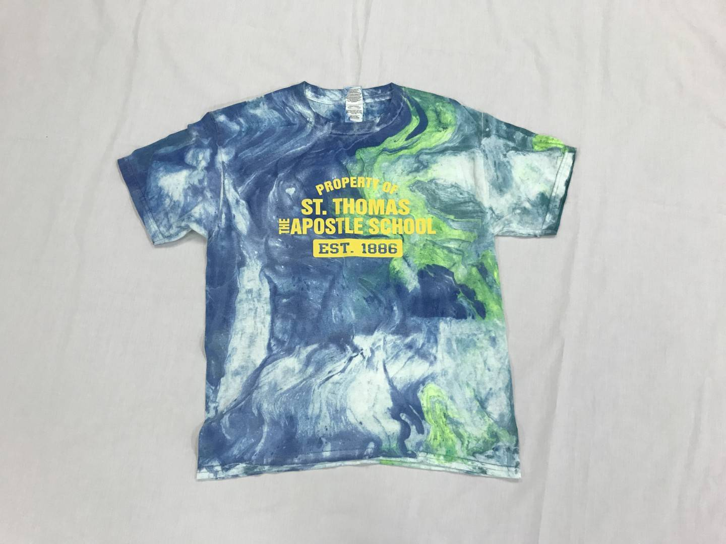 Tie dyed multi color t-shirt with Property of St. Thomas the Apostle logo